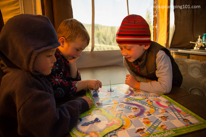 kids playing a board game inside a popup camper